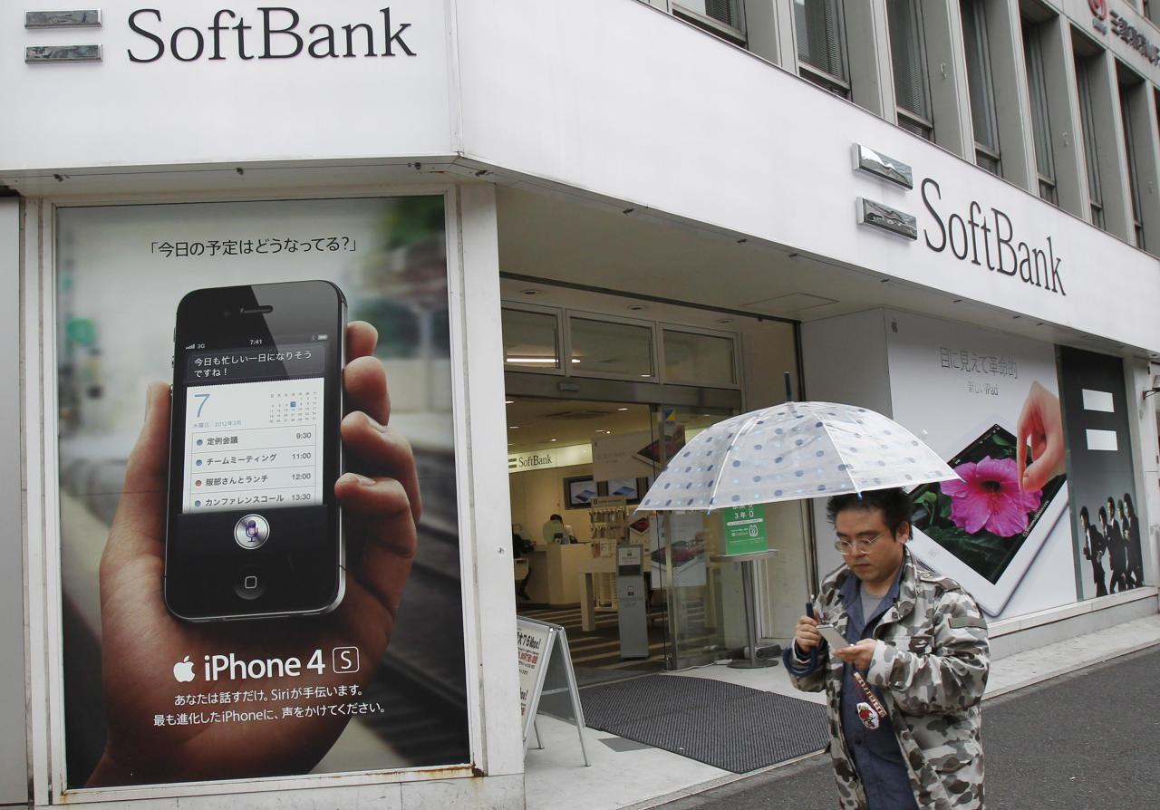 A man uses his mobile phone while walking by a Softbank shop in Tokyo Thursday, April 26, 2012. Japanese mobile carrier Softbank Corp. reported a surge in annual profit because of strong demand for Apple's iPhone 4S. Softbank reported on Thursday annual profit of 313.8 billion yen ($3.9 billion), up 65 percent from 189.7 billion yen the previous year. Annual sales jumped nearly 7 percent to 3.2 trillion yen ($39.5 billion). (AP Photo/Koji Sasahara)