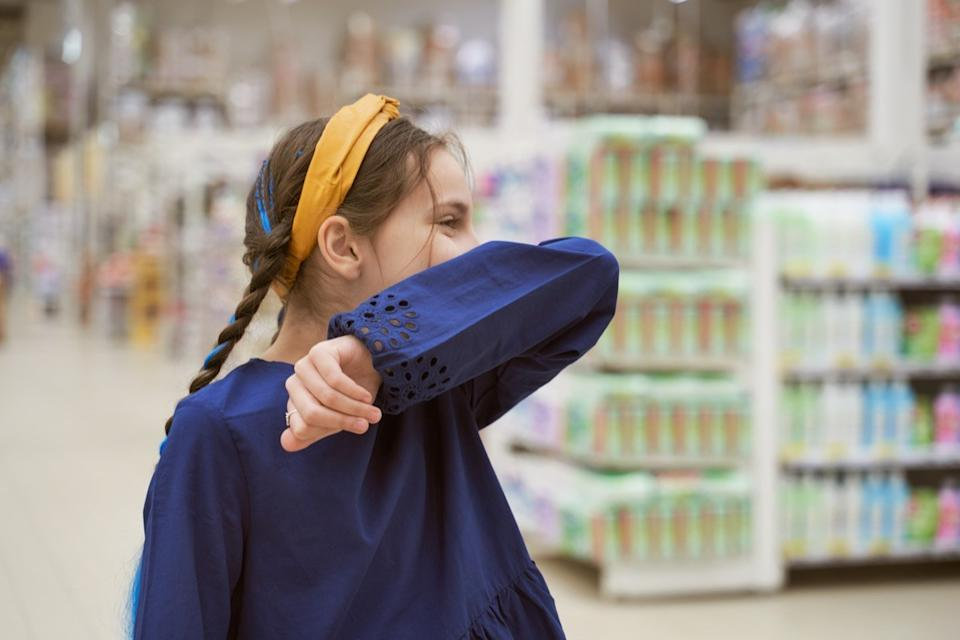 Girl sneezing in store covering with her elbow
