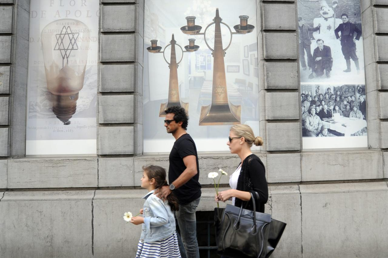 A family brings flowers at the Jewish Museum, site of a shooting in central Brussels May 25, 2014. Belgian police were hunting on Sunday for an assailant who shot dead three people at the Jewish Museum in Brussels, and French authorities tightened security at Jewish sites following another attack that prompted fears of a rise in anti-Semitism. REUTERS/Eric Vidal (BELGIUM - Tags: CRIME LAW)