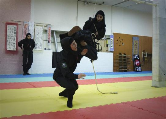 A Ninjutsu practitioner swings from a rope to attack as members of various Ninjutsu schools showcase their skills to the media in a gym at Karaj, northwest of Tehran, February 13, 2012.