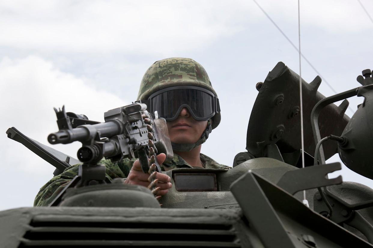 A soldier stands on an armored vehicle as he guards near the Altiplano maximum security prison in Almoloya, west of Mexico City, Sunday, July 12, 2015. (AP Photo/Marco Ugarte)