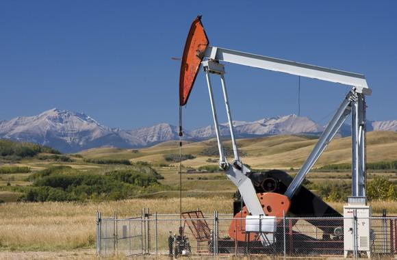 An oil pump with mountains in the background.
