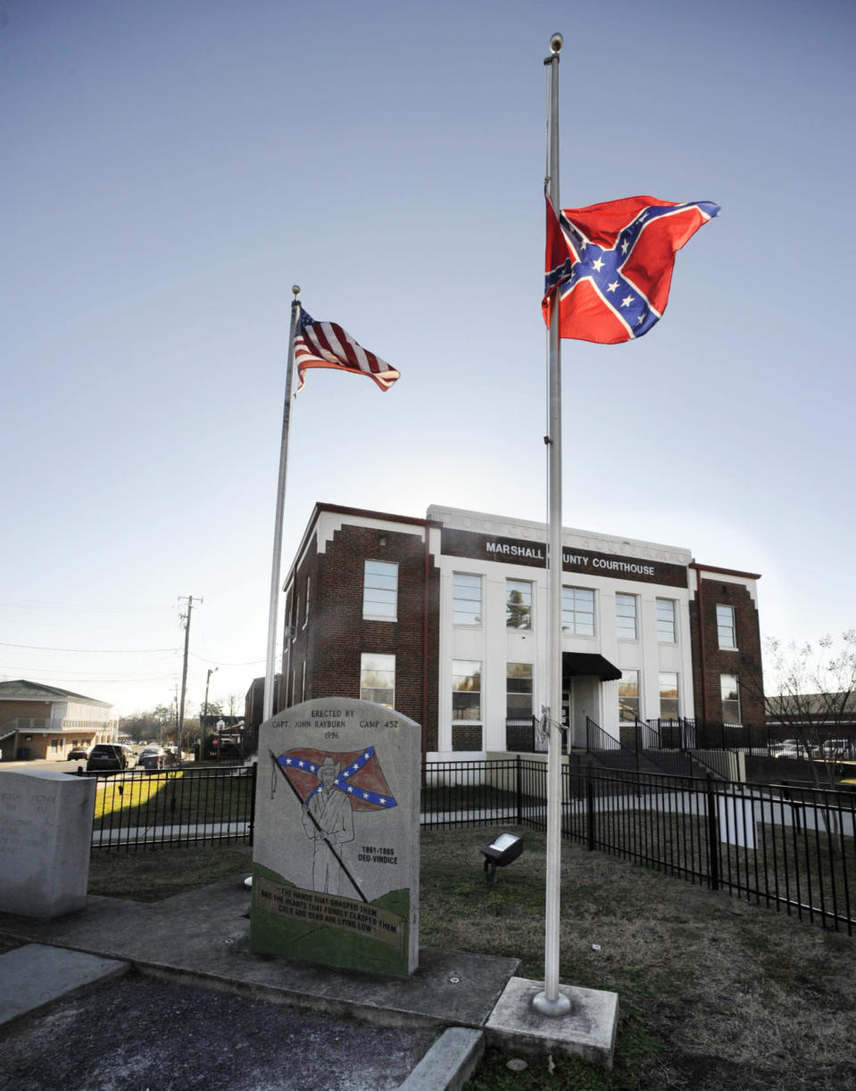 A Confederate monument and rebel battle flag are flown outside the Marshall County Courthouse in Albertville, Ala., on Wednesday, Dec. 9, 2020. Unique Morgan Dunston, a Black woman transformed by leaving the virtually all-white town where she grew up, has been leading demonstrations against the Old South commemoration since August. (AP Photo/Jay Reeves)