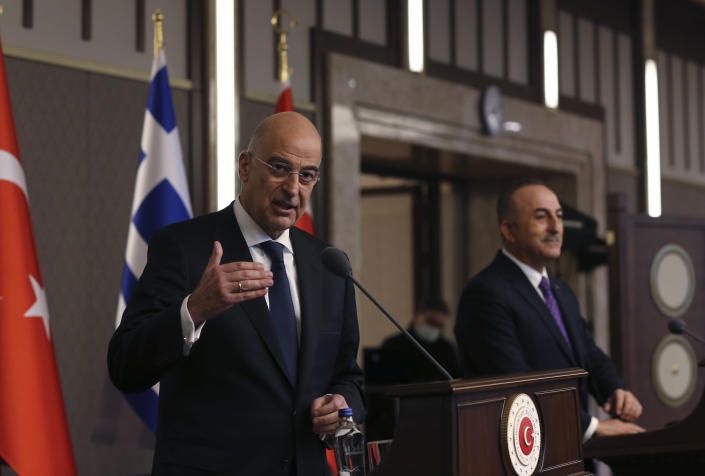 Greek Foreign Minister Nikos Dendias gestures as he talks during a joint media statement with Turkish Foreign Minister Mevlut Cavusoglu, right, following their meeting in Ankara, Turkey, Thursday, April 15, 2021. Dendias visited Ankara Thursday for talks on the two NATO allies' fraught relationship, following a slight easing of tensions between the neighbors. The visit is the first between the two nations following a tumultuous year. (AP Photo/Burhan Ozbilici)