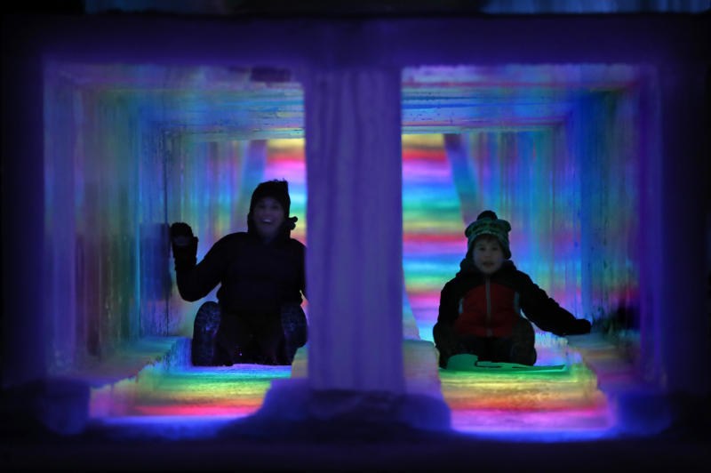 In this Friday, Jan. 25, 2019 photo, visitors race down the side-by-side tunnels of a 97-foot ice slide at Ice Castles in North Woodstock, N.H. The winter wonderland is one of six in North America. (AP Photo/Robert F. Bukaty)