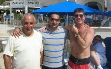 Mansoor Hussain posing with Sir Philip Green and Simon Cowell while on holiday