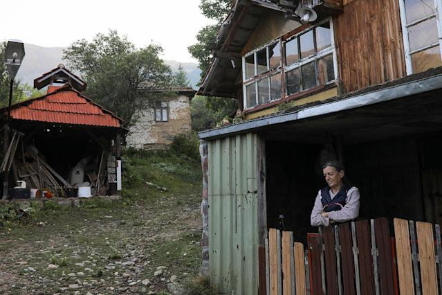 """<p>Vida, the last woman living in the village of Ravno Bucje, stands in front of her home, near the south-eastern town of Knjazevac, Serbia, August 15, 2016. Her husband Bosko died last year and although it is very remote and has hard winters, she wants to stay in the village. Her daughter lives in Knjazevac and brings Vida things she need once a month. She lives in the village with a dog and two cats. REUTERS/Marko Djurica SEARCH """"DEPOPULATION"""" FOR THIS STORY. SEARCH """"WIDER IMAGE"""" FOR ALL STORIES. – RTS1CYDX </p>"""