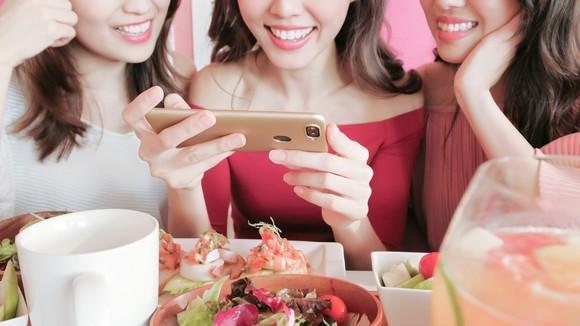 Three women take photos of their food with a smartphone.