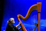 "A harpist practices ahead of of an outdoor performance of ""La Boheme"" in Palm Beach"
