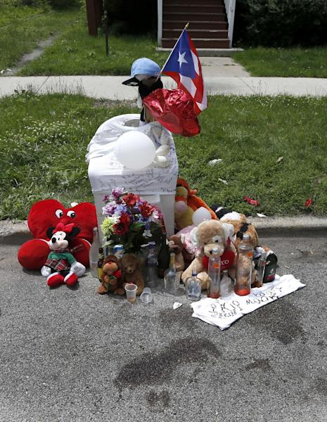 Blood stains and a make shift memorial for 18-year-old Jamal Jones is seen where police found him with gunshots wounds to the shoulder and chest over the past weekend, on Chicago's Southside, Monday, June 17, 2013. Chicago Police are investigating several shootings after a violent weekend that left at least seven people dead, including Jones, and more than three dozen wounded. (AP Photo/Charles Rex Arbogast)