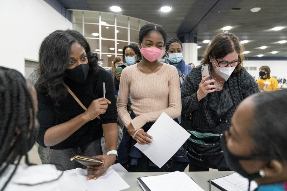 Denice Asbell, left, brings her daughter Rhegan, 13, center, down to the central counting board to observe democratic election challengers watching ballots being counted in the early morning hours of Wednesday, Nov. 4, 2020 in Detroit. (AP Photo/David Goldman)