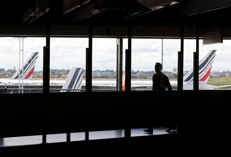 A passenger walks as Air France planes are parked on the tarmac at Orly Airport near Paris as Air France pilots, cabin and ground crews unions call for a strike over salaries