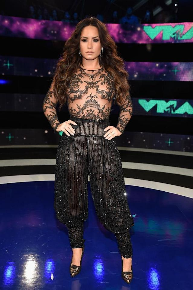 <p>Demi Lovato, who performed the national anthem at the Mayweather versus McGregor fight in Las Vegas the night before, stepped out in a one-piece suit with two totally different personalities. On the top, the number featured a sheer shirt, while the bottom included glitter harem pants. (Photo: Getty Images) </p>