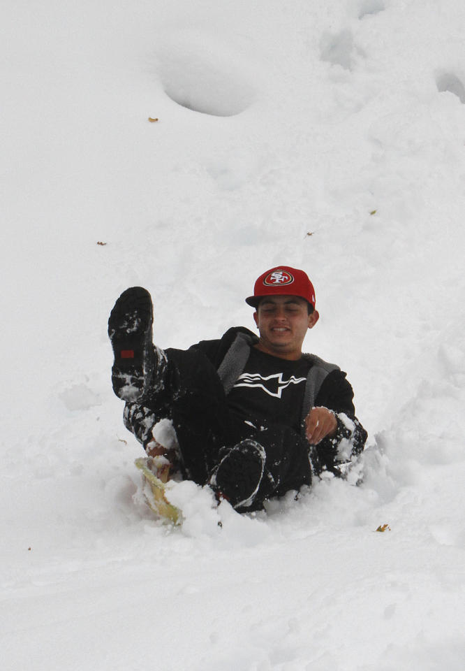 Chris Gilbert sleds down a slop on freshly fallen snow near Blue Canyon, Calif., Monday, Oct. 22, 2012. The first storm of the season swept through Northern California bringing rain to the lower elevations and snow in the mountains. (AP Photo/Rich Pedroncelli)