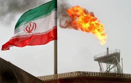 FILE PHOTO: A gas flare on an oil production platform in the Soroush oil fields is seen alongside an Iranian flag in the Gulf July 25, 2005. REUTERS/Raheb Homavandi/File Photo/File Photo