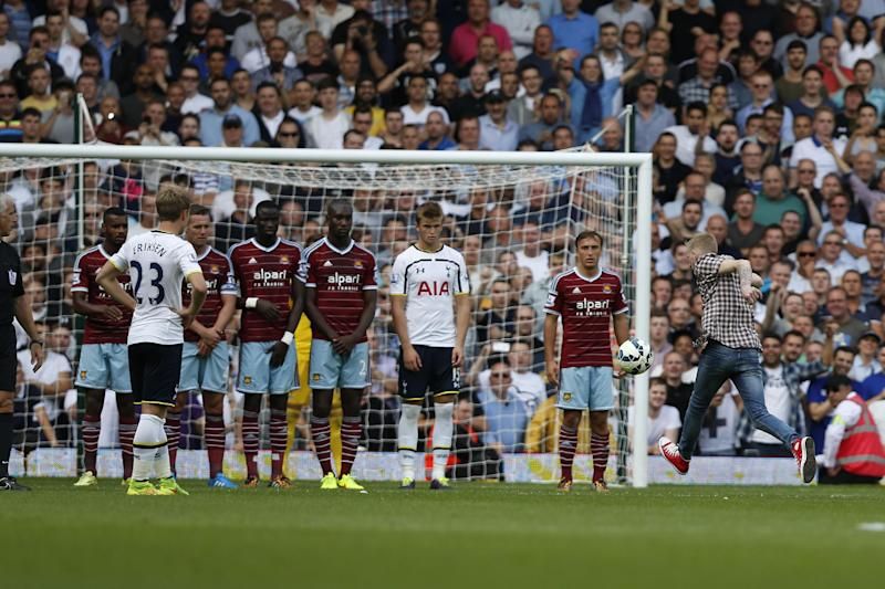 A supporter runs onto the pitch and kicks the ball set up for a Tottenham Hotspur's free kick against West Ham United during their English Premier League soccer match at Upton Park, London, Saturday, Aug. 16, 2014