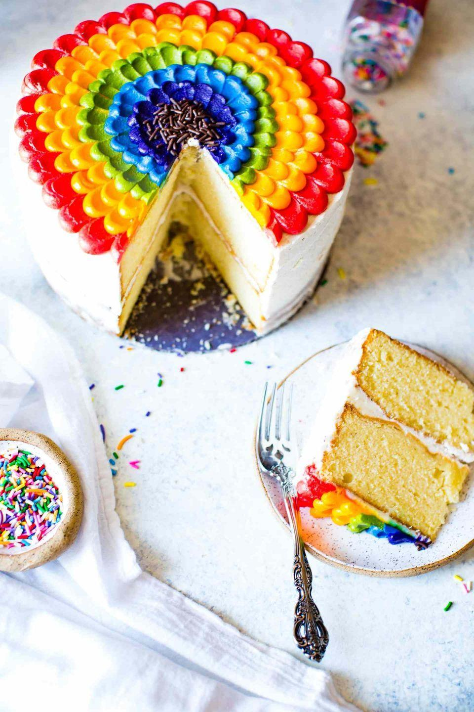 """<p>It's all about the decorations with this rainbow vanilla cake. While the blogger admits the petal design is a little time-consuming, it's still surprisingly easy to create.</p><p><strong>Get the recipe at <a href=""""https://www.butterbeready.com/vanilla-almond-rainbow-petal-cake/"""" rel=""""nofollow noopener"""" target=""""_blank"""" data-ylk=""""slk:Butter Be Ready"""" class=""""link rapid-noclick-resp"""">Butter Be Ready</a>.</strong></p><p><strong><a class=""""link rapid-noclick-resp"""" href=""""https://go.redirectingat.com?id=74968X1596630&url=https%3A%2F%2Fwww.walmart.com%2Fsearch%2F%3Fquery%3Dpiping%2Bbags&sref=https%3A%2F%2Fwww.thepioneerwoman.com%2Ffood-cooking%2Fmeals-menus%2Fg36421919%2Frainbow-recipes%2F"""" rel=""""nofollow noopener"""" target=""""_blank"""" data-ylk=""""slk:SHOP PIPING BAGS"""">SHOP PIPING BAGS</a><br></strong></p>"""