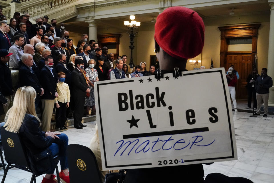"""A supporter wears a """"Black Lies Matter"""" sign as Georgia Gov. Brian Kemp speaks during a news conference at the State Capitol on Saturday, April 3, 2021, in Atlanta, about Major League Baseball's decision to pull the 2021 All-Star Game from Atlanta over the league's objection to a new Georgia voting law. (AP Photo/Brynn Anderson)"""