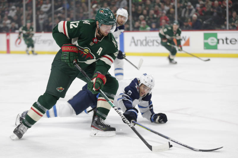 Minnesota Wild center Eric Staal controls the puck in front of Winnipeg Jets defenseman Luca Sbisa in the first period of an NHL hockey game Saturday, Dec. 21, 2019, in St. Paul, Minn. (AP Photo/Andy Clayton-King)
