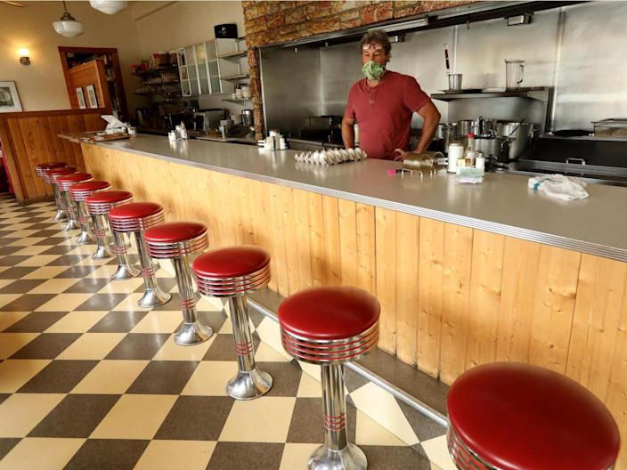 Travis Medlock, owner of Little Shop of Ramen, looks over a row of empty stools inside his restaurant along Highway 140 in the heart of Mariposa on April 29, 2020