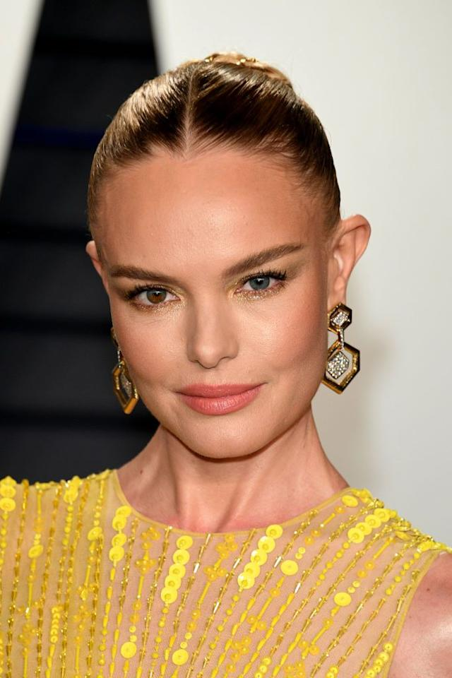 <p>Kate Bosworth had her hair pulled back into a sleek and shiny chignon that had golden strong woven throughout. It mirrored her dress and glittery golden eyeshadow.</p>