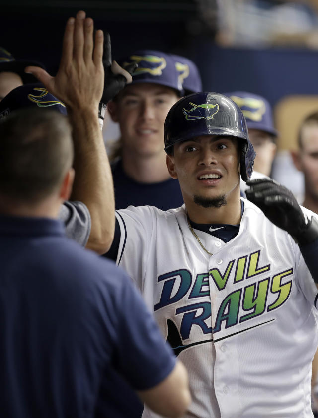 Tampa Bay Rays' Willy Adames high fives teammates in the dugout after his home run off New York Yankees starting pitcher Sonny Gray during the seventh inning of a baseball game Saturday, June 23, 2018, in St. Petersburg, Fla. (AP Photo/Chris O'Meara)