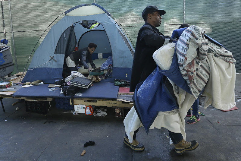 A homeless couple gather their belongings at a tent camp in San Francisco. Half the money that the newly passed Proposition C generates will go toward building permanent housing for homeless residents. (ASSOCIATED PRESS)