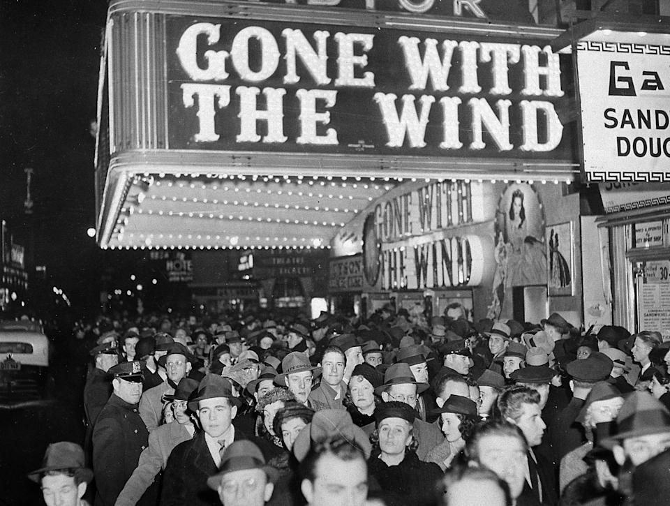 "A crowd gathers under the ""Gone With the Wind"" marquee outside the Astor Theater on Broadway during the movie's premiere in New York City on Dec. 19, 1939.  The movie also opened at the Capitol Theater a few blocks north.  (AP Photo)"