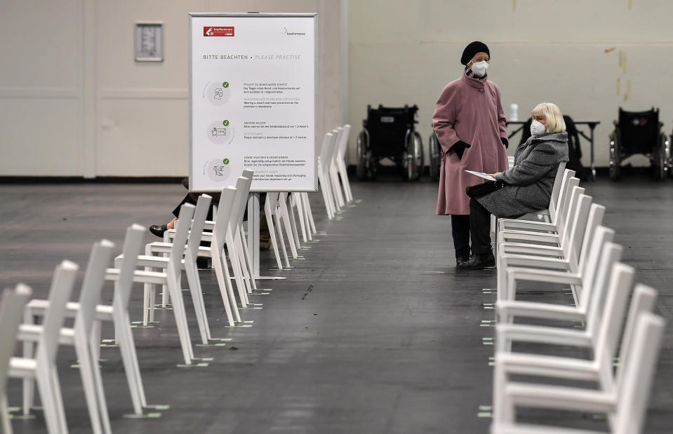 People sit in waiting area at the opening of the vaccination for the BioNTech-Pfizer vaccination against COVID-19 disease in Cologne, Germany, Monday, Feb. 8, 2021. Vaccination against the coronavirus started for senior citizens outside care homes today in Germany's most populated province North Rhine-Westphalia. (AP Photo/Martin Meissner)