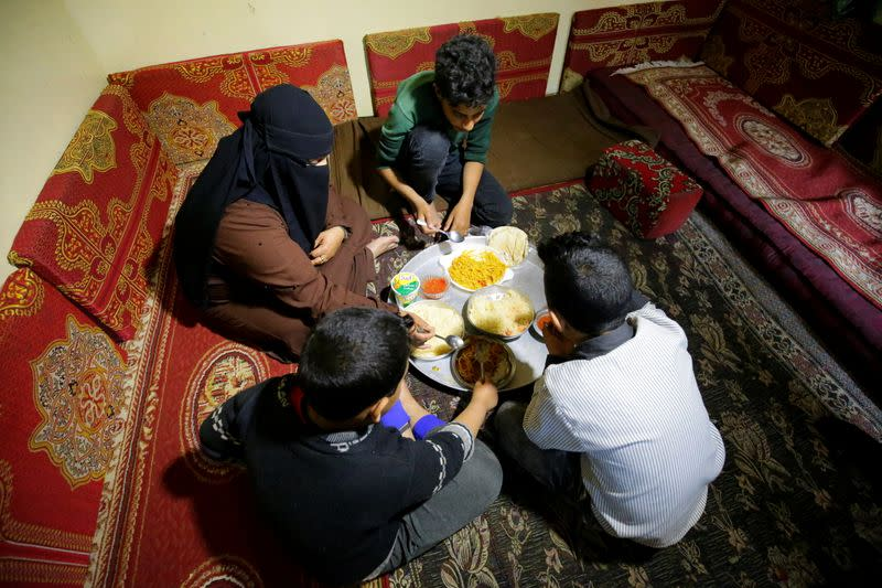 Mona Muhammad and her sons sit for a meal at their house in Sanaa