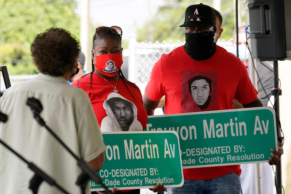<p>Sybrina Fulton, center and Tracy Martin, parents of Trayvon Martin, hold street signs with their son's name, Thursday, Nov. 5, 2020, in Miami Gardens, Fla. The street on the way to Martin's former school was renamed in his honor, eight years after he was killed by a neighborhood watch volunteer in Sanford, Fla. </p> ((AP Photo/Marta Lavandier))