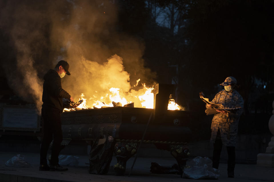 Residents burn paper offerings to a relative who died from the coronavirus on the eve of the anniversary of the 76-day lockdown in the central Chinese city where the coronavirus was first detected in Wuhan in central China's Hubei province, Friday, Jan. 22, 2021. (AP Photo/Ng Han Guan)