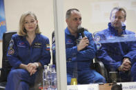 In this handout photo released by Roscosmos, actress Yulia Peresild, left, director Klim Shipenko, right, and cosmonaut Anton Shkaplerov, members of the prime crew of Soyuz MS-19 spaceship attend a news conference at the Russian launch facility in the Baikonur Cosmodrome, Kazakhstan, Monday, Oct. 4, 2021. In a historic first, Russia is set to launch an actress and a film director to space to make a feature film in orbit. Actress Yulia Peresild and director Klim Shipenko are set to blast off Tuesday for the International Space Station in a Russian Soyuz spacecraft together with Anton Shkaplerov, a veteran of three space missions.(Roscosmos Space Agency via AP)