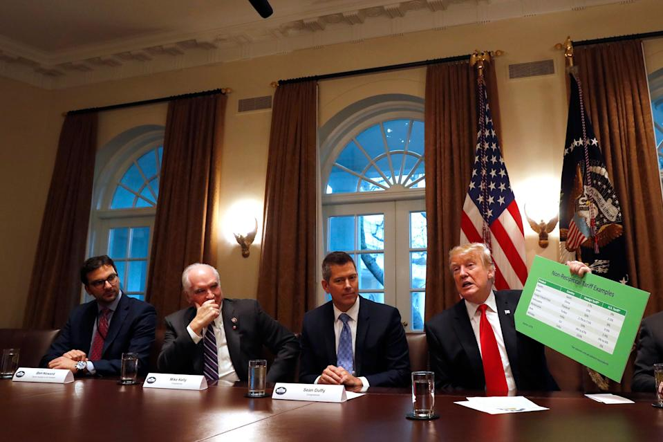 President Donald Trump holds up examples of tariffs, Thursday, Jan. 24, 2019, as he speaks in the Cabinet Room of the White House in Washington. (AP Photo/Jacquelyn Martin)