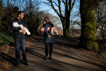 Adi, 37, who works for a removal company, and wife Maria, 31, take their daughters, Elena, who is two years and seven-months old and baby Ioana, who is less than a week old, for a walk in Hampstead Heath, near their home in London, Britain, February 3, 2019. REUTERS/Alecsandra Dragoi