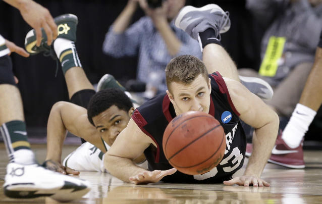 Harvard's Evan Cummins, right, and Michigan State's Alvin Ellis III eye a loose ball in the first half during the third round of the NCAA men's college basketball tournament in Spokane, Wash., Saturday, March 22, 2014. (AP Photo/Elaine Thompson)