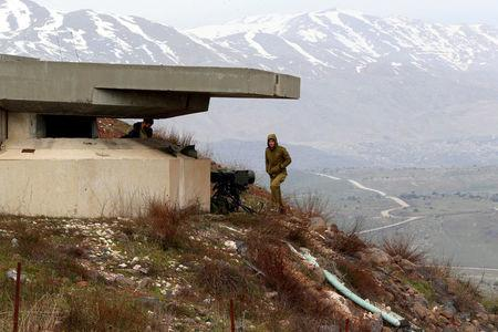 FILE PHOTO - An Israeli soldier walks near a military post close to the Druze village of Majdal Shams in the Israeli-occupied Golan Heights