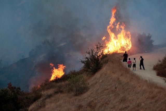 <p>People look on at the La Tuna Canyon fire over Burbank, Calif., Sept. 2, 2017. (Photo: Kyle Grillot/Reuters) </p>