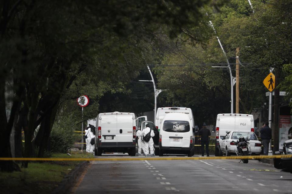 Forensic investigators and police work the scene where security secretary, Omar García Harfuch, was attacked by gunmen in the early morning hours in Mexico City, Friday, June 26, 2020. Heavily armed gunmen attacked and wounded Mexico City's police chief in a brazen operation that left an unspecified number of dead, Mayor Claudia Sheinbaum said Friday. (AP Photo/Rebecca Blackwell)