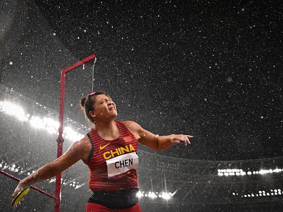 China's Chen Yang throws a discus in the rain at the Tokyo Olympics.
