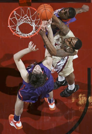 Florida State's Xavier Gibson (1) gets between Clemson's Catalin Baciu, bottom, and Devin Coleman, top, for a tip-in during the first half of an NCAA college basketball game on Sunday, March 4, 2012, in Tallahassee, Fla. (AP Photo/Phil Sears)