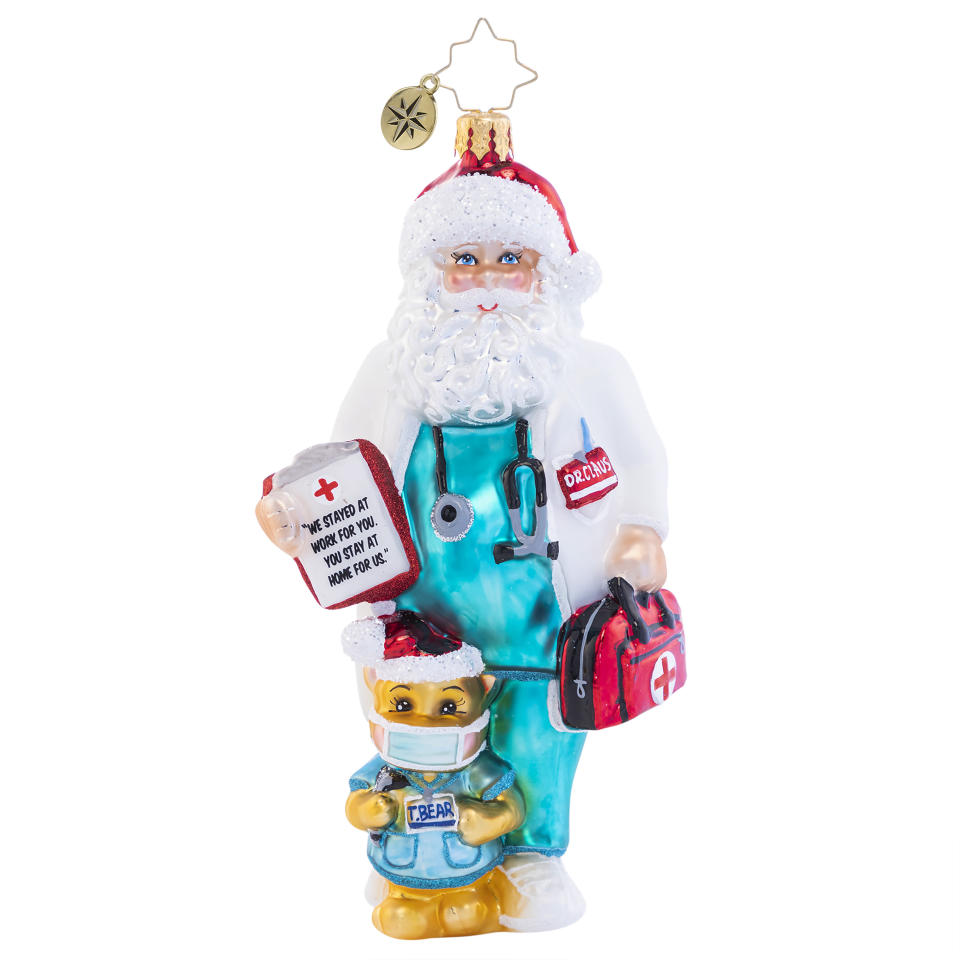 """This image shows a Christopher Radko holiday ornament of a Santa in scrubs holding a message: """"We stayed at work for you. You stay at home for us."""" (Christopher Radko via AP)"""