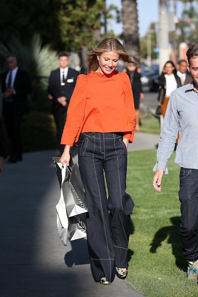 <p>Gwyneth attended a Nordstrom event in 2017 wearing an orange blouse, wide-leg jeans, and floral platform sandals.</p>