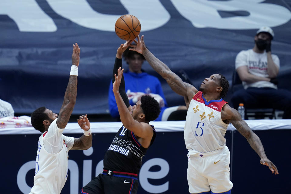 Philadelphia 76ers forward Mike Scott (12) shoots between New Orleans Pelicans guard Eric Bledsoe (5) and forward James Johnson in the second half of an NBA basketball game in New Orleans, Friday, April 9, 2021. (AP Photo/Gerald Herbert)