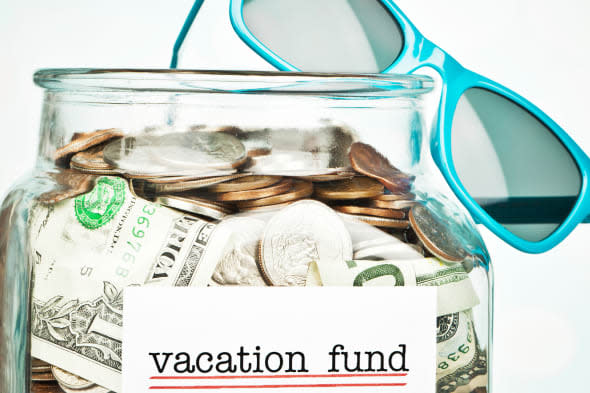Sunglasses and money jar filled with savings for vacation.