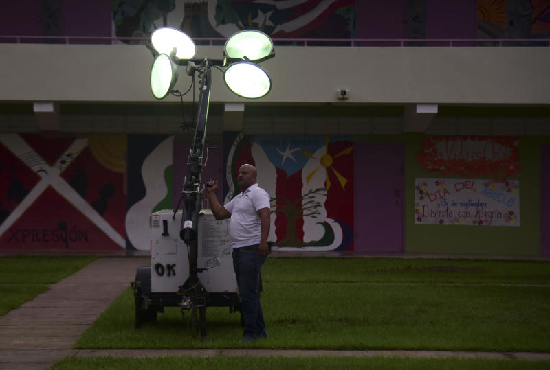 A municipal worker turns on portable lights atthe inner courtyard of Ramon Quinones Medina High School, one of the shelters enabled by the municipality of Yabucoa before the arrival of Tropical Storm Karen, in Yabucoa, Puerto Rico, Tuesday, Sept. 24, 2019. (AP Photo/Carlos Giusti)