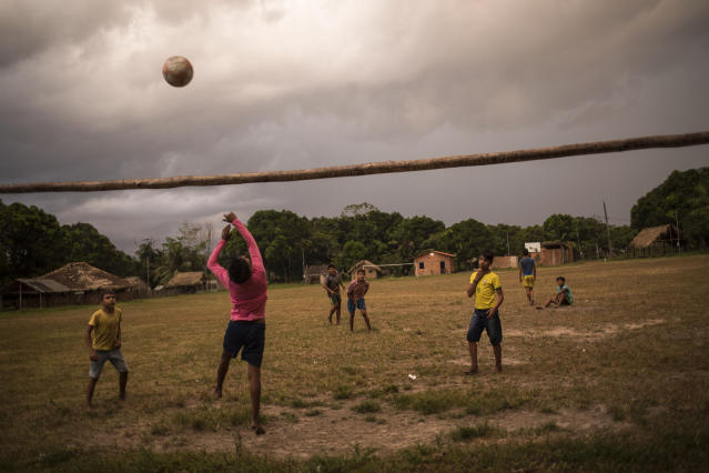 In this Sept. 2, 2019 photo, Tembe boys play soccer on a field in the Cajueiro village, Para state, Brazil. During the rite of passage into adulthood, that can last for days, tribe members hunt monkeys and birds that they later cook, while the young jump, sing and mimic bird sounds with other members of the tribe inside a communal hut to banging of feet on the floor and the shaking of rattles. (AP Photo/Rodrigo Abd)