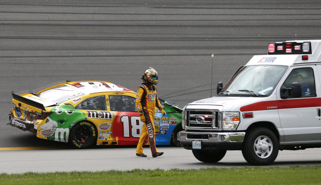 Driver Kyle Busch (18) walks to an ambulance past his wrecked race car during a NASCAR Sprint Cup series auto race at Kansas Speedway in Kansas City, Kan., Sunday, Oct. 6, 2013. (AP Photo/Orlin Wagner)