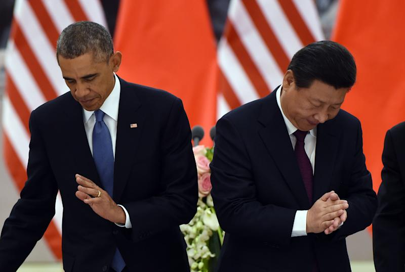 US President Barack Obama (L) returns to his seat as Chinese President Xi Jinping applauds after a toast at a lunch banquet in the Great Hall of the People in Beijing on November 12, 2014
