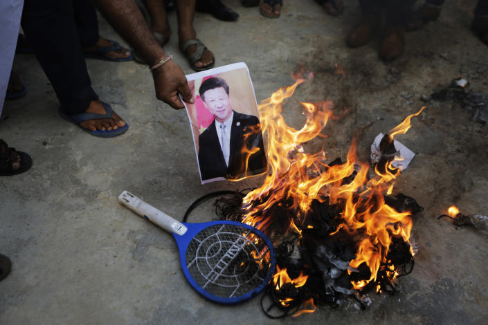 An Indian man burns a photograph of Chinese president Xi Jinping during a protest against China in Ahmedabad, India, Tuesday, June 16, 2020. At least three Indian soldiers, including a senior army officer, were killed in a confrontation with Chinese troops along their disputed border high in the Himalayas where thousands of soldiers on both sides have been facing off for over a month, the Indian army said Tuesday. (AP Photo/Ajit Solanki)